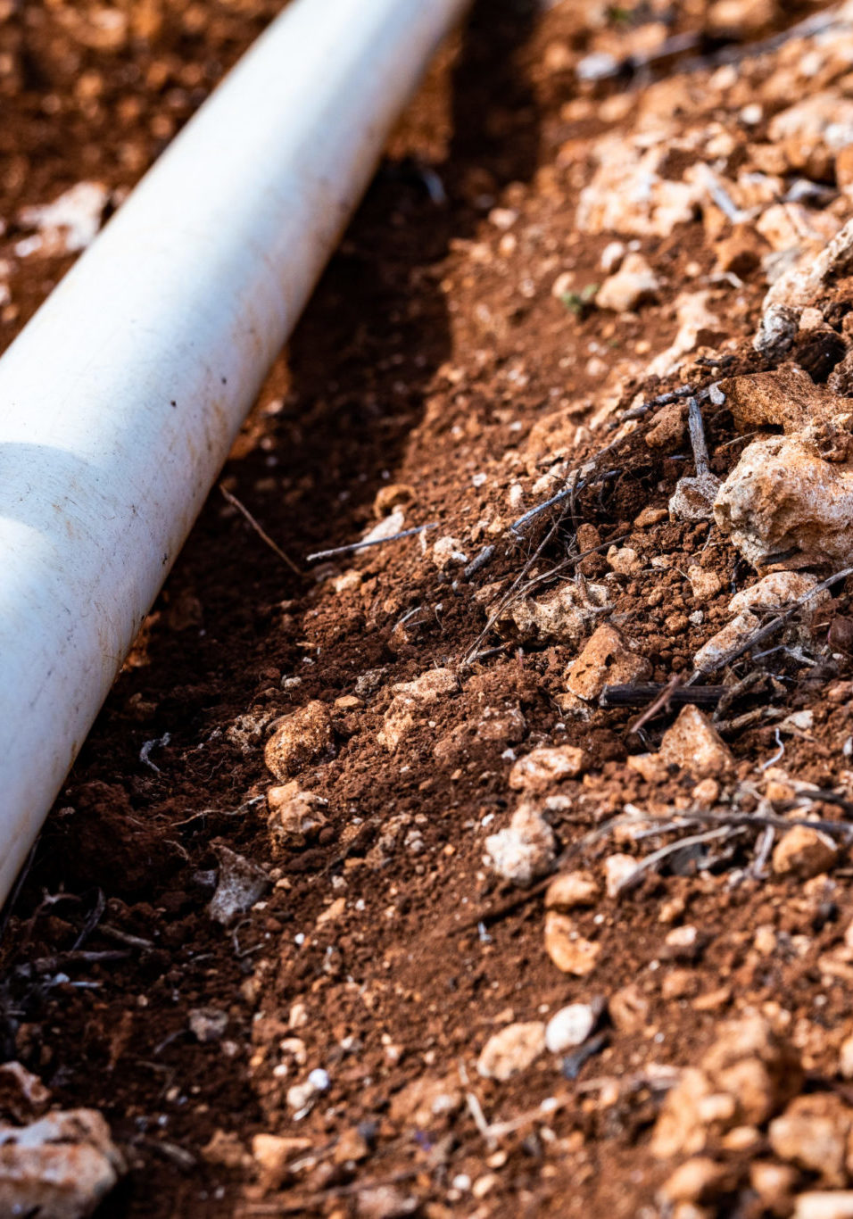 PVC pipe in dirt trench outdoors for plumbing water drainage installation. Underground irrigation system.